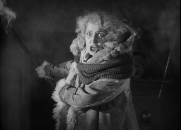 Gerda Lundqvist as Fru Samzelius in the silent movie adaptation of Gösta Berling's Saga. Distraught and disheveled, dressed in piecemeal fur rags, she carries a torch, ready to burn her own home to the ground rather than hand it over to her enemies.
