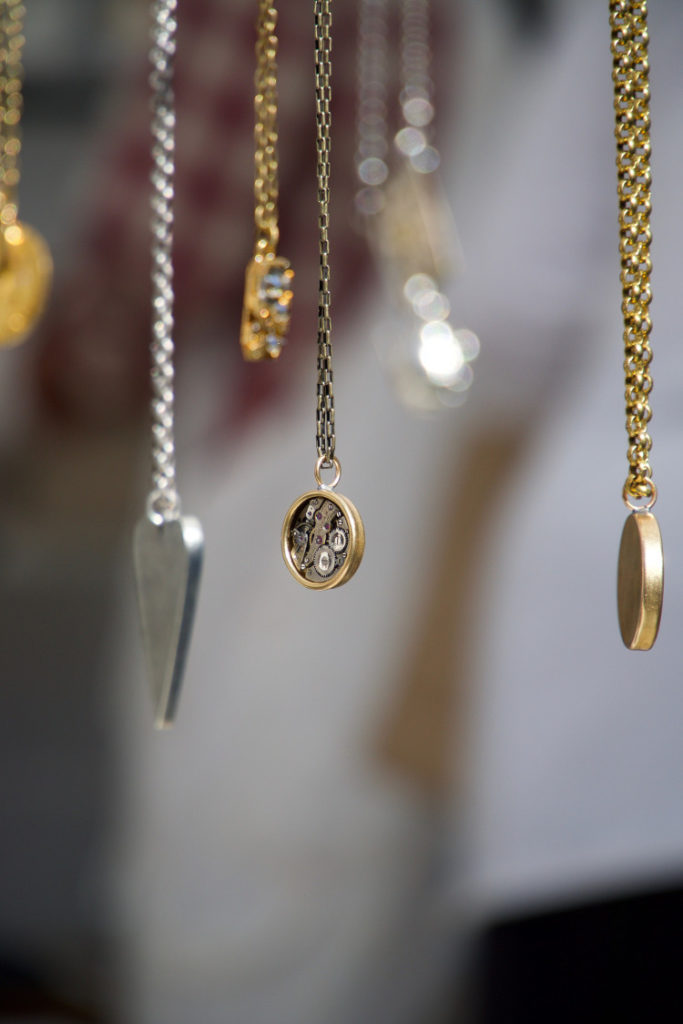 Gold and silver Victorian fascinators and lockets suspended from an unseen hand or display.