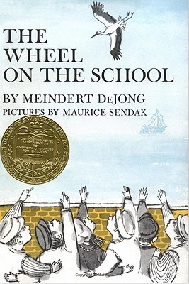 "Cover of Meindert deJong's ""The Wheel on the School"" featuring a watercolor illustration by Maurice Sendak of five young boys and one girl in traditional Dutch clothing standing in front of a yellow wall, pointing and looking at a stork flying against a clear blue sky."