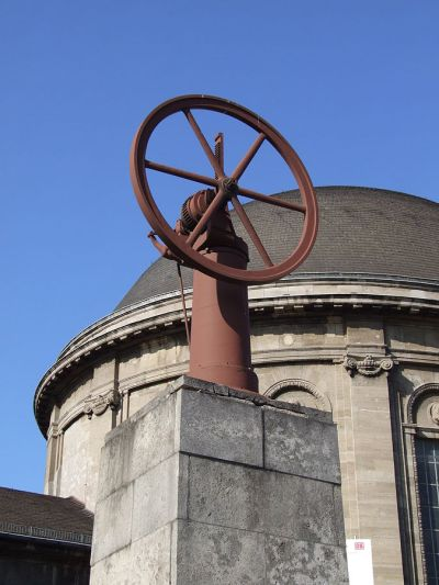 """En originaler """"atmosphärischer Gasmotor"""" zur Erinnerung an Nicolaus Otto am Deutzer Bahnhof Bild: Tohma [CC BY-SA 4.0 (https://creativecommons.org/licenses/by-sa/4.0)]"""