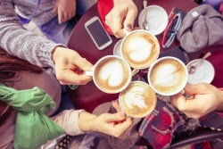 four hands holding coffee cups with hearts and tree designs in froth