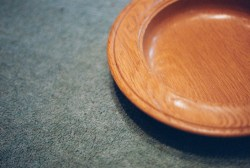 Partial view of wooden offering plate on carpeted surface.