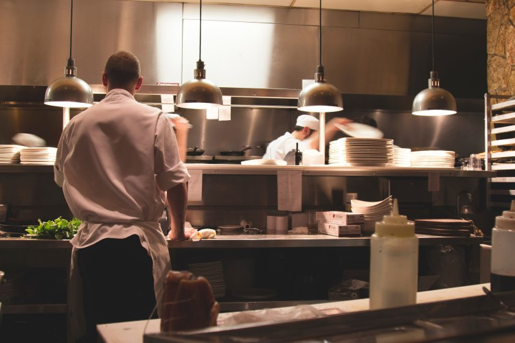 restaurant kitchen picture showing server in foreground and chef in background.