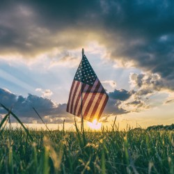 American flag in green grassy field a sunset with partly cloudy sky.