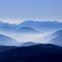 blue tinted image of multiple mountain ranges