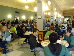 large cafeteria showing sitting customers and line of waiting customers