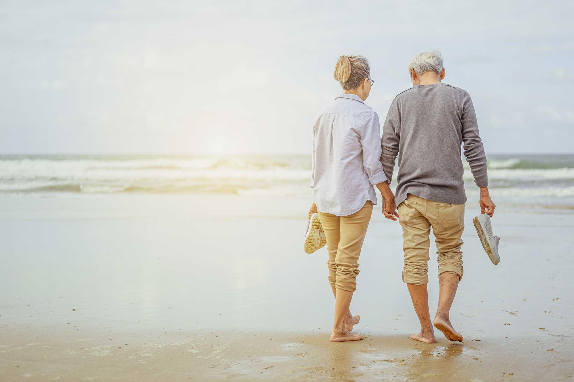 Retireees walking on beach at Kohlnhofer Insurance Agency