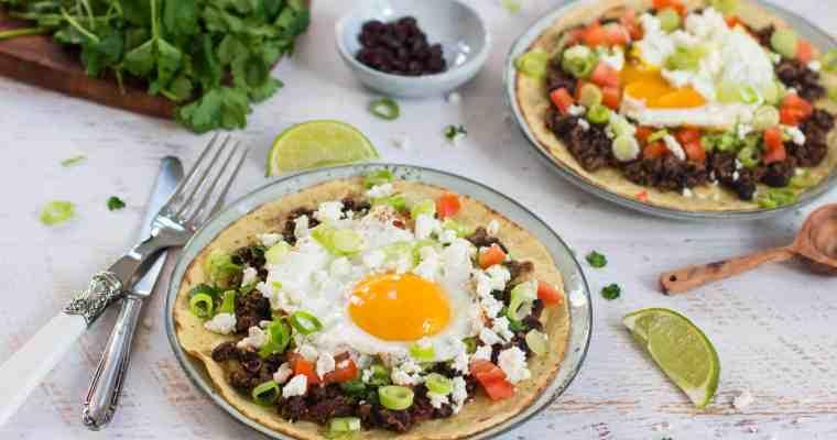 Tostada's met zwarte bonen, avocado en een gebakken eitje