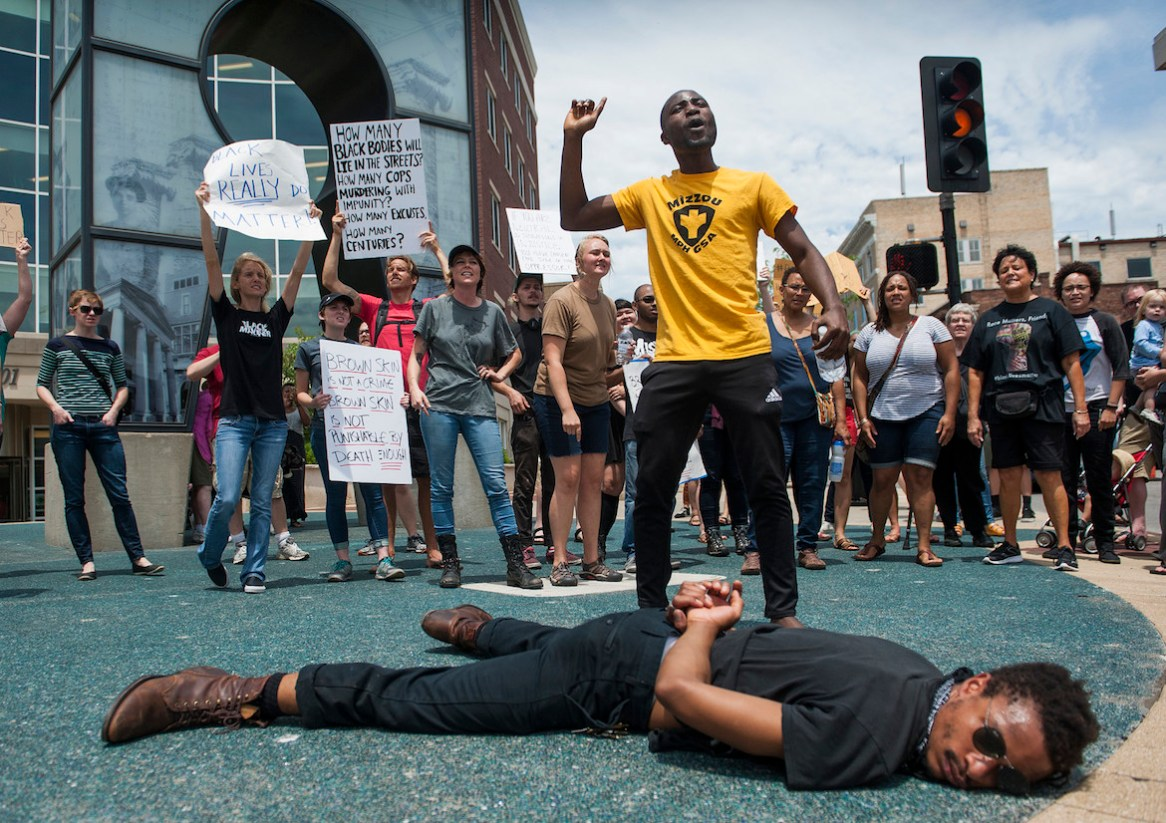 Ola Aromaye, center, chants as he and Jamie Davis, bottom, protest the shooting this week in Baton Rouge, La., of Alton Sterling, Thursday, July 7, 2016 in front of City Hall in Columbia, Mo. Protesters from Black Lives Matter and other groups and individuals marched through the streets. Sterling was shot at close range after being pinned down by two officers.(Daniel Brenner/Columbia Daily Tribune via AP)