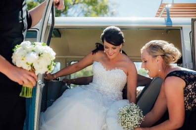 Bride in Vintage 1960s Volkswagen Kombi Van being assisted out of Hire Car by Bridesmaid Wedding Day