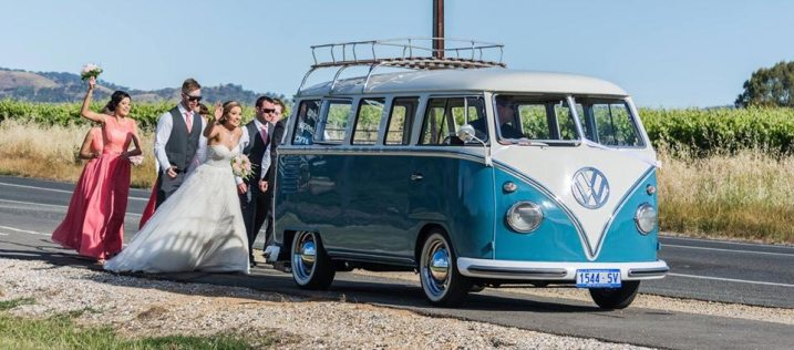 Bridal Party chasing classic hire car, 1960s blue Volkswagen Kombi Van in front of vineyards in Adelaide South Australia