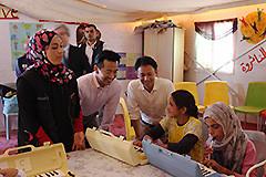 鍵盤ハーモニカを練習する児童と交流する谷合、岡本の両氏=28日 ヨルダンのザアタリ難民キャンプ