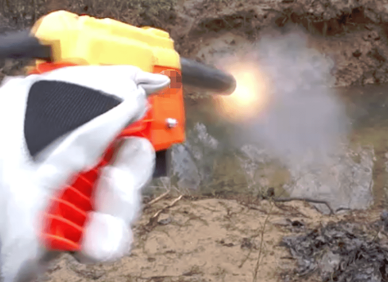 Still frame of the dart blaster being fired in a controlled environment