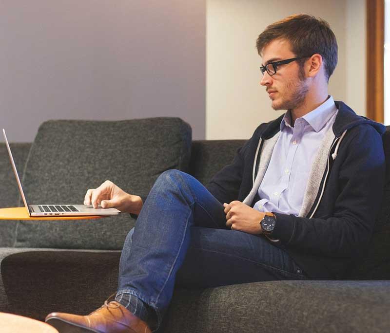 Mann sitter i sofa med en Acer Chromebook R13 forran seg på et bord