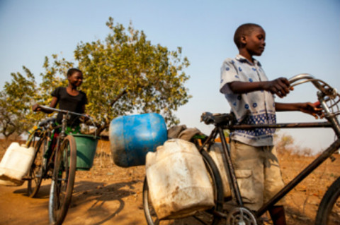 Putting innovative ideas into action: Two Malawian siblings wheel bicycles loaded with buckets to collect water from a community bore-hole as part of the 'What if bikes could recycle?' idea. Competition at Universities around the World