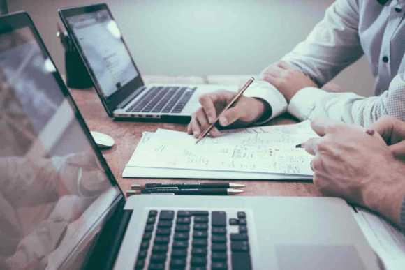 KontextLiga baut mit Kunden produktive Partnerschaften auf, in denen wir gemeinsam strategisch, effizient und effizient Ziele verfolgen. © by helloquence @ unsplash: Hände mit Stiften arbeiten an einem Papier zwischen Laptops