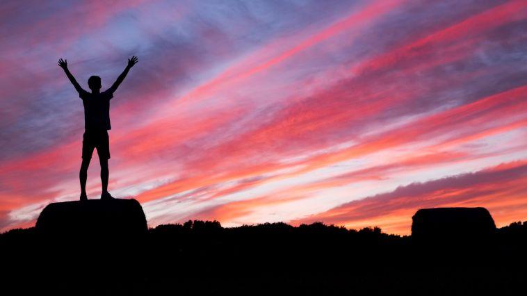 gün batımında kollarını açıp sevinen insan