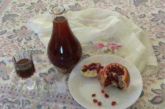 Pomegranate Liqueur in a glass and bottle photo