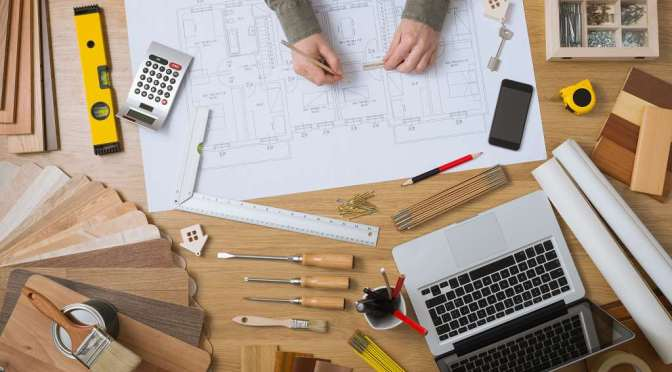 Construction engineer and architect's desk with house projects, laptop, tools and wood swatches top view, male hands drawing