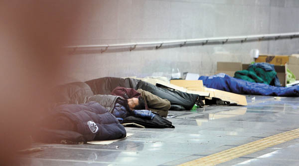 Homeless people sleep near Seoul Station in Jung District, central Seoul.