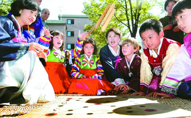 A group of children dressed in traditional Hanbok play the traditional four-stick board game, yutnori, on Seollal. Provided by Korea.net