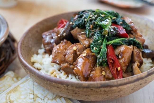 Chicken stir fry with kale and mushrooms in a brown ceramic bowl