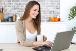 Beautiful young woman using her laptop in the kitchen.