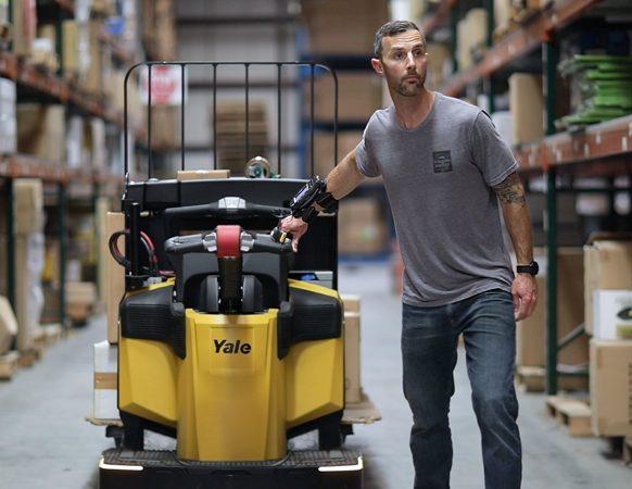 Warehouse worker pulls a lift truck