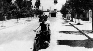 """Η κεντρική είσοδος του Σταδίου της ΑΕΚ από την οδό Χρυσοστόμου Σμύρνης. Αριστερά ο δενδοφυτευμένος ευρύς χώρος που περιέβαλε τον μη αποπερατωμένο το έτος 1957 Ιερό Ναό της Αγίας Τριάδος. Δεξιά διακρίνεται η πυκνή δενδροστοιχία και το φαρδύ πεζοδρόμιο προ των κατοικιών του Μικρασιατοπροσφυγικού συνοικισμού. Πηγή: """"Αναζήτηση Αγοράς"""", Απρίλιος 2008"""