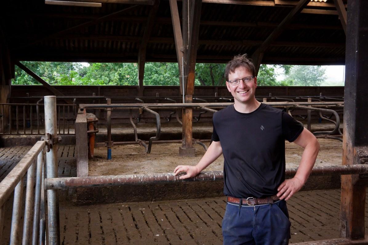 Jan-Hendrik Langeloh im noch leeren Laufstall. Vor dem Tor warten die Kühe darauf, reingelassen zu werden.