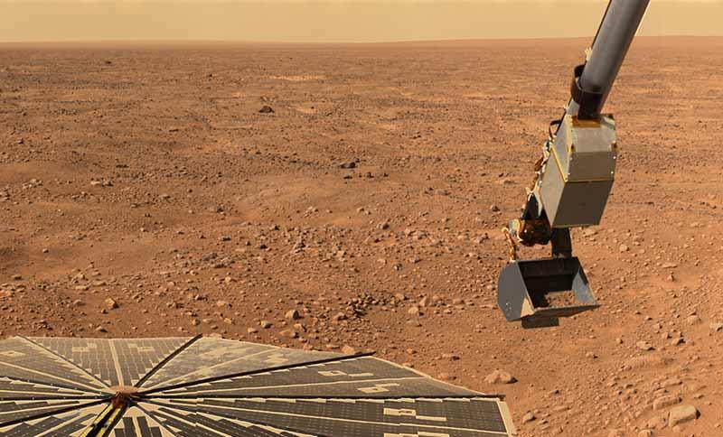 Phoenix'in kameralarından Mars yüzeyi, aracın Güneş panelleri ve kazıcı kepçesi.