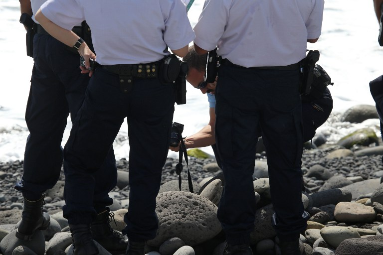 Police officers inspect and photograph metallic debris found on a beach in Saint-Denis on the French Reunion Island in the Indian Ocean on August 2, 2015, close to where where a Boeing 777 wing part believed to belong to missing flight MH370 washed up last week.  A piece of metal was found on La Reunion island, where a Boeing 777 wing part believed to belong to missing flight MH370 washed up last week, said a source close to the investigation.  Investigators on the Indian Ocean island took the debris into evidence as part of their probe into the fate of Malaysia Airlines flight MH370, however nothing indicated the piece of metal came from an airplane, the source said.  AFP PHOTO / RICHARD BOUHET