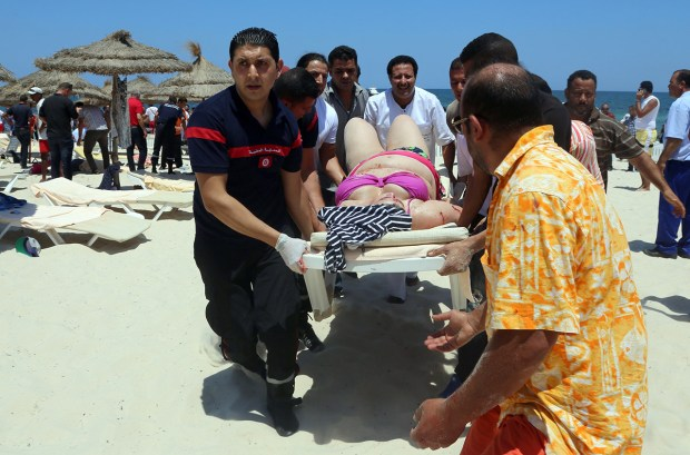 TOPSHOTS Tunisian medics carry a woman on a stretcher in the resort town of Sousse, a popular tourist destination 140 kilometres (90 miles) south of the Tunisian capital, on June 26, 2015, following a shooting attack. At least 27 people, including foreigners, were killed in a mass shooting at a Tunisian beach resort packed with holidaymakers, in the North African country's worst attack in recent history. AFP PHOTO / FETHI BELAID