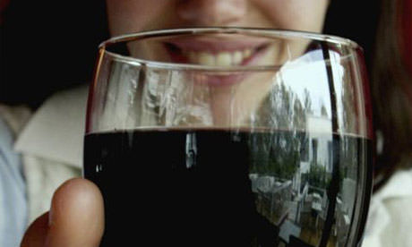 A young Greek woman tastes red Greek wine