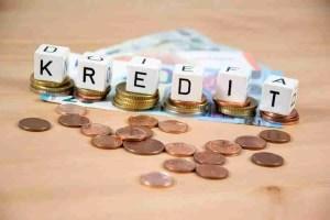 Weiße Würfel mit der Aufschrift Kredit auf Münzen und auf Geldscheinen. Kredit mit schneller Auszahlung