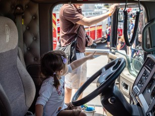 A little girl excited by what's outside her truck.