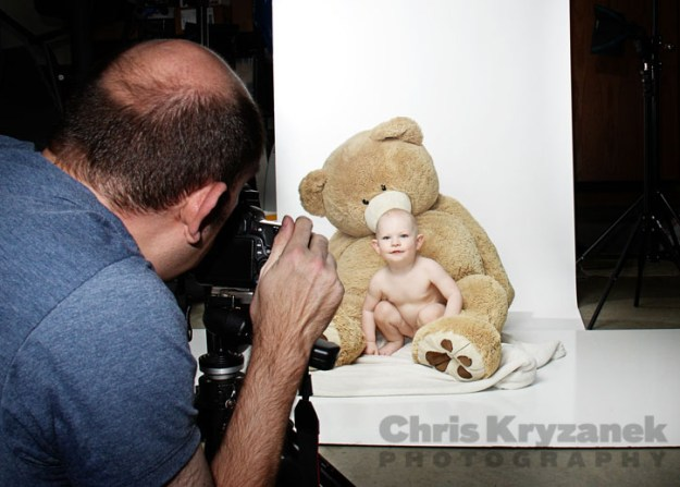 Behind the scenes photographing a baby with a giant stuffed bear
