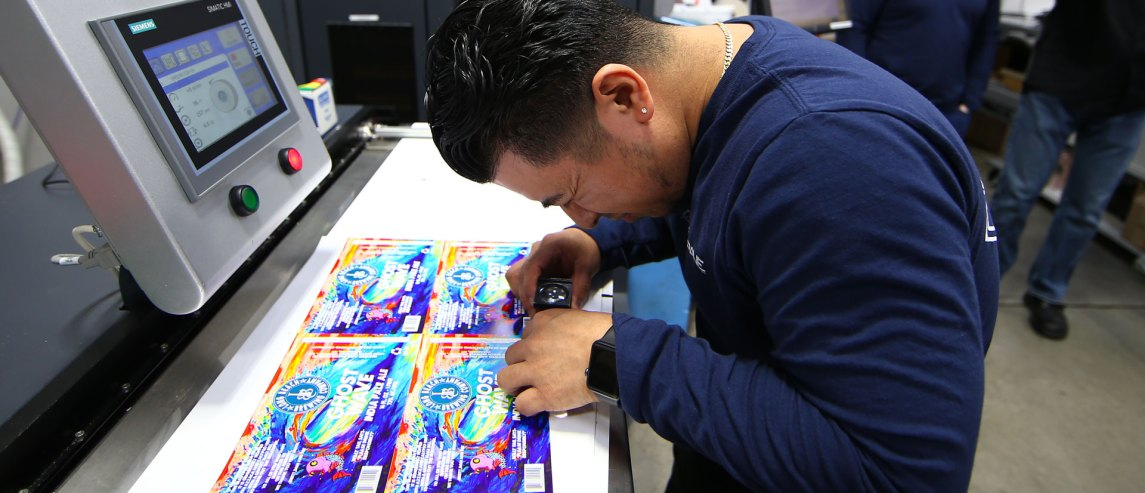 press operator checking beer labels