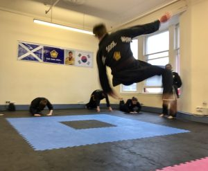 Black belt candidate performing a high break fall (Nak Bup)