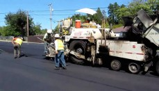 Workers resurface a road with asphalt