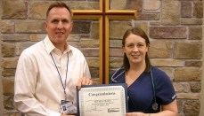 Nevada Fields (right) receives the Wright Memorial Hospital Employee of the Quarter Award for third quarter 2018 from Steve Schieber (left), CEO