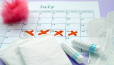 Menstrual pads and tampons on menstruation period calendar with red cross marks lies on lilac background
