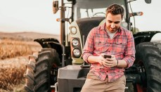 Young man holding phone standing by Tractor in field