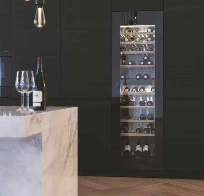 The luxurious wine cabinet WineCooler V6000 impresses with its particularly aesthetic design and space for around 83 bottles of wine. The diffuse lighting contributes to the noble character in the kitchen room. (Photo: V-ZUG)