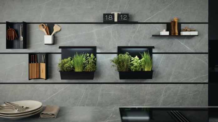 """The intelligent niche system """"next125 cube"""" knows how to use the space between upper and lower cabinets in a clever way. A panel with fine stainless steel profiles serves as a suspension for all kinds of kitchen helpers. (Photo: next125)"""