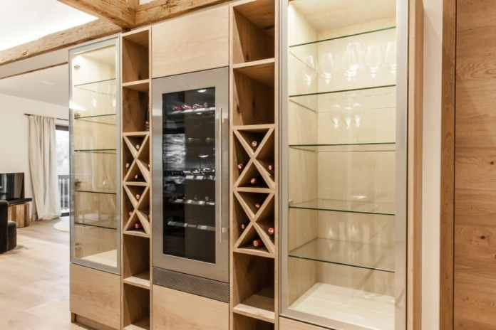 A Liebherr wine refrigerator, lined with a drinks cabinet and showcases, is the heart of Tyrolean cuisine.  Atmospheric LED lighting and decorative glass fronts loosen up the design optically and make the massive cabinet look like living room furniture.  (Photo: The Kitchen Club)
