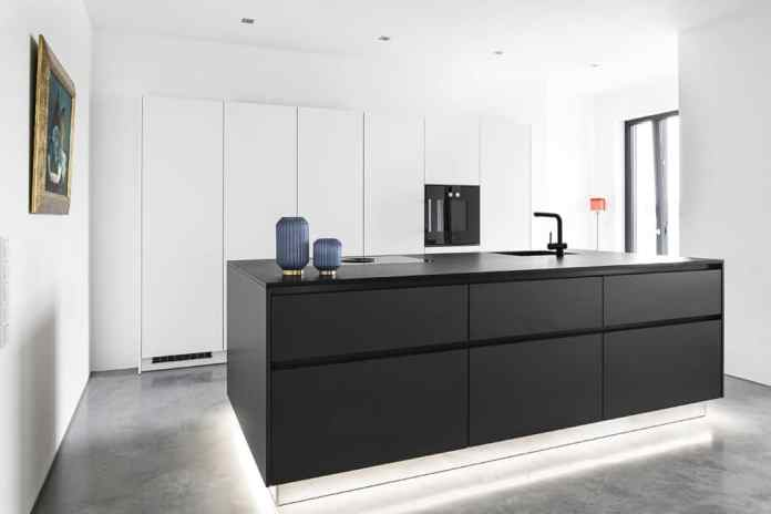 Like yin and yang, the narrow, handleless tall unit wall in matt white and the monumental, black kitchen island come together.  A special highlight is the raised underbody lighting of the cooking block.  (Photo: Dross & Schaffer Ingolstadt)