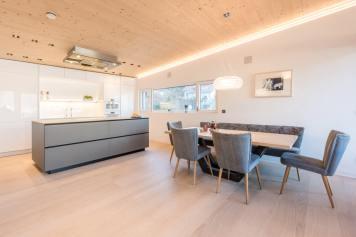 Grau-weiße Küche in einem Penthouse über den Dächern von Innsbruck. Foto: Schwab Küchen Salzburg