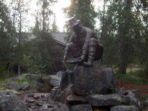 Kullankaivaja patsaan takana on Härkäselästä siirretty rakennus, jossa on viimeksi sijainnut kivi- ja mineraalinäyttely.