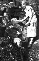 Linnea Hepo-oja leipoo Miessijoen kodin pihallla olevassa kiviuunissa.
